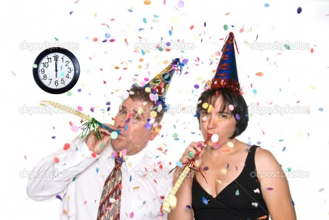 Couple celebrates a happy New Years Eve occassion by wearing party hats and blowing horns under falling confetti