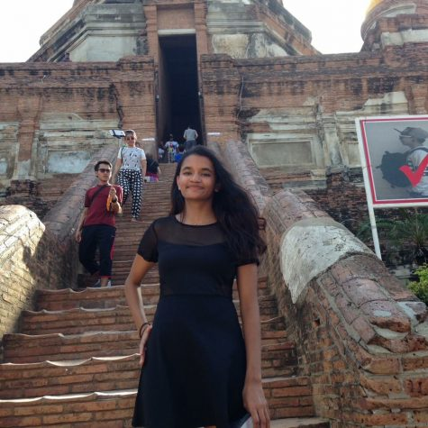 Anu stands at the foot of a buddhist temple in Thailand.