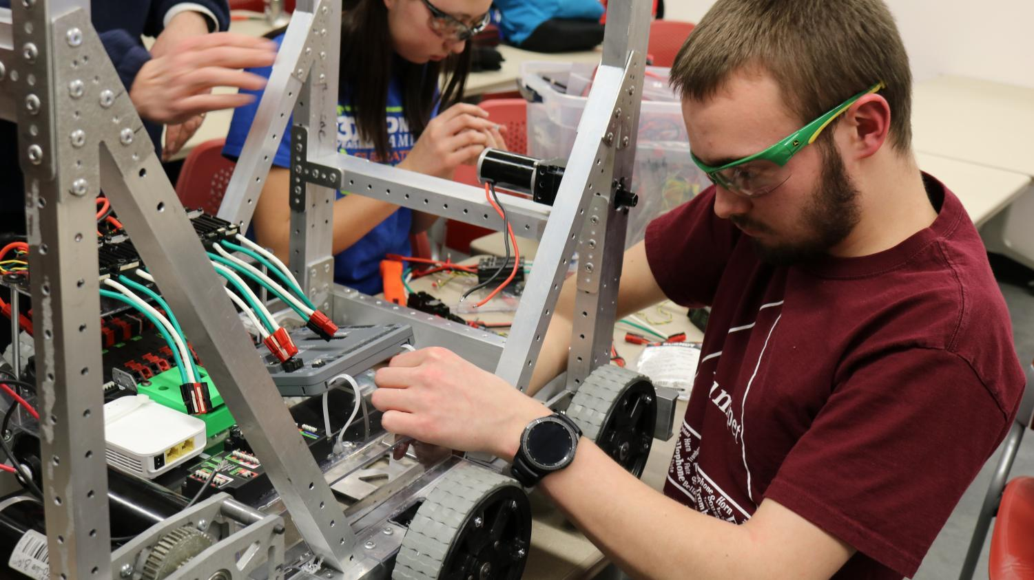 Senior Joel Neppl examines the wiring of the team robot.