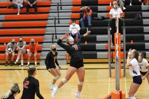(Photo taken by Olivia Sassman) Junior Alexa Kopaska wears her mask as she prepares for a spike.