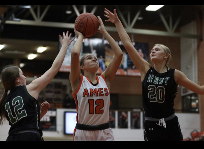 Ames Senior Leah Tietjens goes for a shot guarded by two  West players