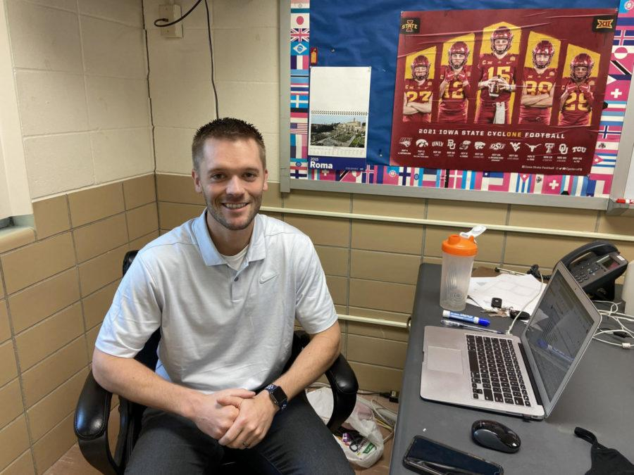 Mr. Landhauser sitting at his desk in his classroom.